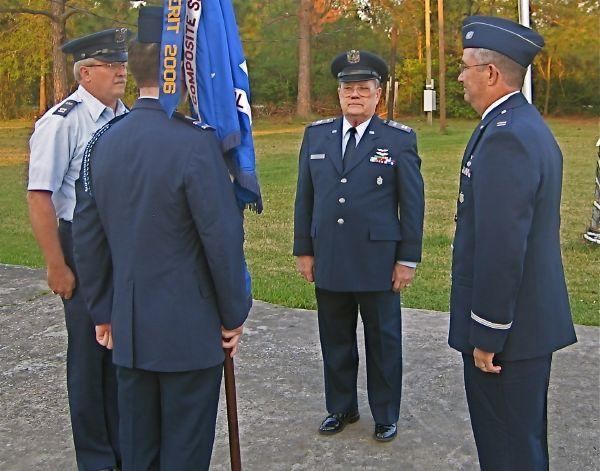 The Civil Air Patrol Delta Composite Squadron guidon, symbol of command, has just been passed from Capt. Dan Katen (far left) to Capt. Risher Lewis (far right). Observing is CAP Group IV Deputy Commander Capt. Bob Beeley.